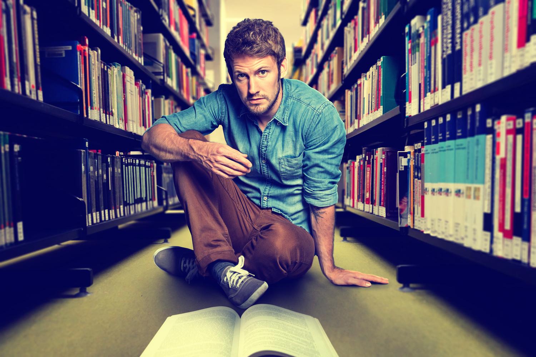 Student zwischen Regalen mit Büchern in Bibliothek